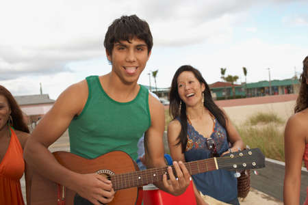 bathingsuit: Young Hispanic man playing guitar