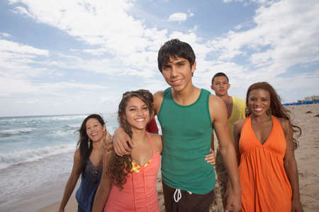 ice chest: Multi-ethnic friends walking on beach