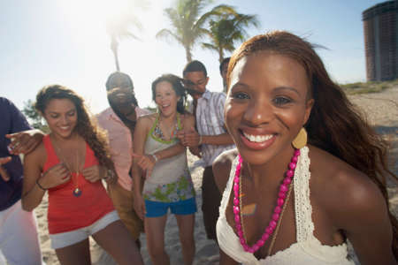 vacationing: Hispanic woman with friends in background LANG_EVOIMAGES