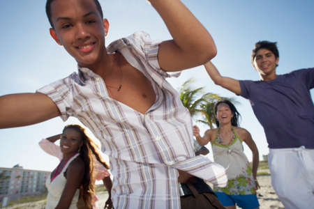 teenaged boy: Hispanic teenaged boy with friends in background LANG_EVOIMAGES