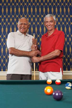 pool cue: Multi-ethnic senior men holding pool cue