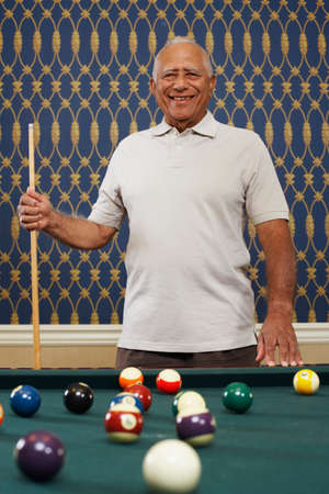 pool stick: Senior Mixed Race man holding pool cue