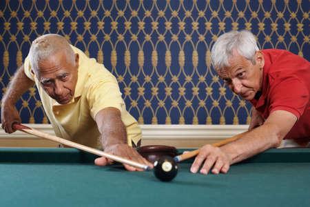 low spirited: Multi-ethnic senior men aiming for same billiard ball LANG_EVOIMAGES