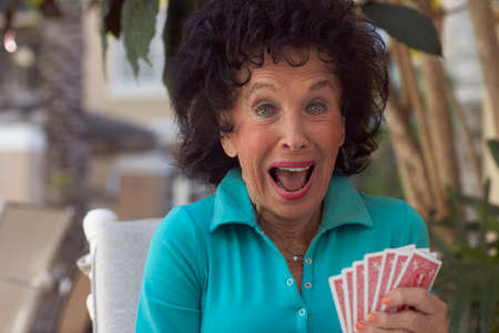 fulfilling: Senior woman playing cards
