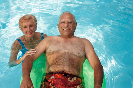 relishing: Multi-ethnic senior couple in swimming pool