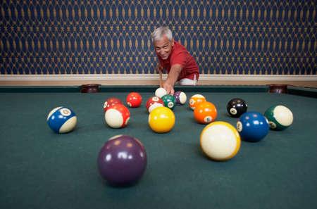 deceiving: Senior man playing pool LANG_EVOIMAGES
