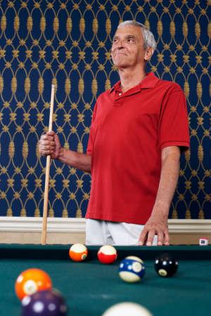 pool cue: Senior man holding pool cue