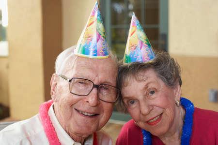 80 plus adult: Senior couple wearing party hats