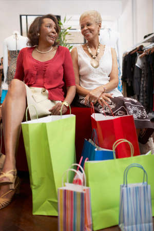shopping buddies: Senior African American women clothes shopping LANG_EVOIMAGES