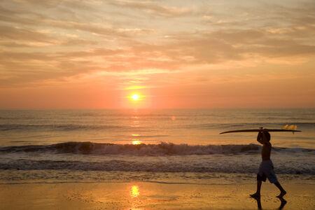 nite: Asian boy carrying surfboard at beach