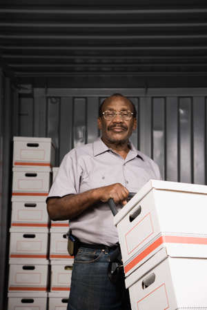 cardboard only: Senior African American male worker with stacks of boxes