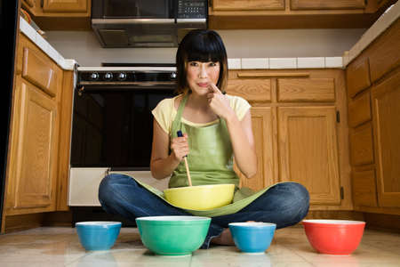 fulfilling: Asian woman with mixing bowls on floor