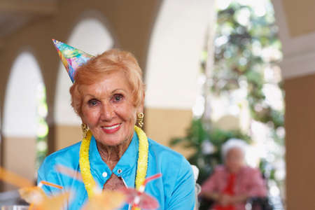 ridiculous: Senior woman wearing party hat LANG_EVOIMAGES