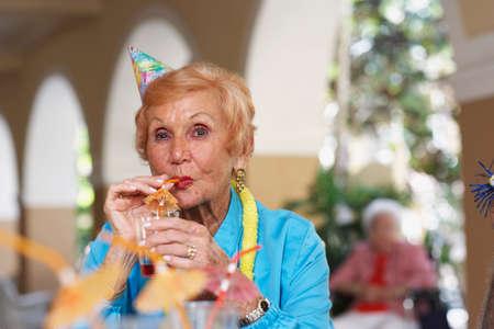 attired: Senior woman drinking cocktail