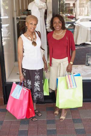 kinfolk: Senior African American women holding shopping bags