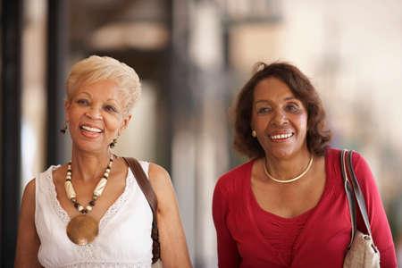 mujeres sentadas: Las mujeres afroamericanas Personas Mayores que llevan bolsos