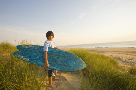 Asian boy holding surfboard at beach