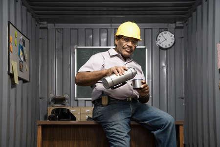 Senior African American male worker drinking coffee