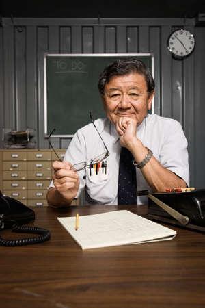 office furniture: Senior Asian businessman at desk LANG_EVOIMAGES