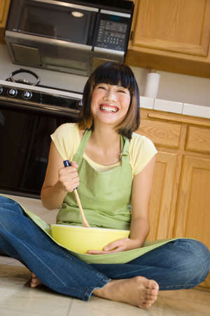 filipino ethnicity: Asian woman mixing batter on floor