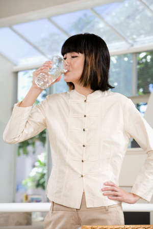 entertaining area: Asian woman drinking glass of water