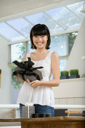 enclosing: Asian woman holding gift LANG_EVOIMAGES