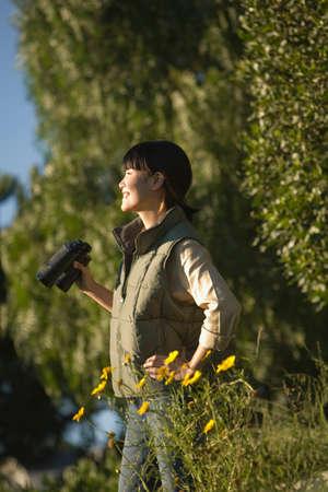 birdwatcher: Asian woman holding binoculars LANG_EVOIMAGES