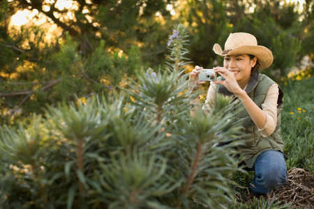 motioning: Asian woman taking photograph of plant