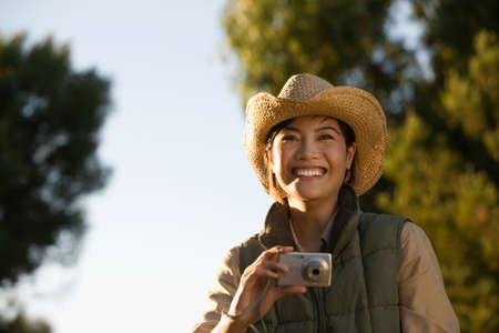 attired: Asian woman holding camera