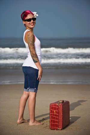 Tattooed Hispanic woman on beach