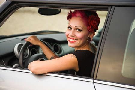 bodyart: Tattooed Hispanic woman in car LANG_EVOIMAGES
