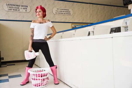 bodyart: Tattooed Hispanic woman in laundromat