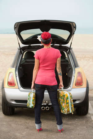 portable rom: Tattooed Hispanic woman holding suitcases