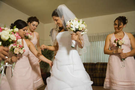 shrieking: Hispanic bride and bridesmaids looking at dress