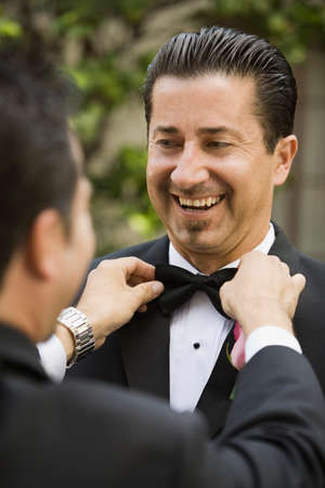 eveningwear: Hispanic man having bowtie adjusted