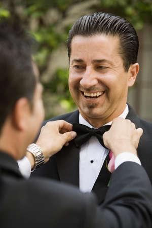 adjusted: Hispanic man having bowtie adjusted