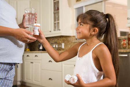 attired: Hispanic girl handing medication to pregnant mother