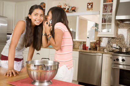 teenaged girls: Hispanic teenaged girls telling secret LANG_EVOIMAGES