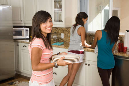 teenaged girls: Hispanic teenaged girls washing dishes LANG_EVOIMAGES