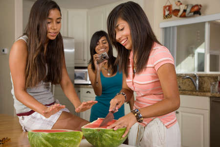 teenaged girls: Hispanic teenaged girls cutting watermelon