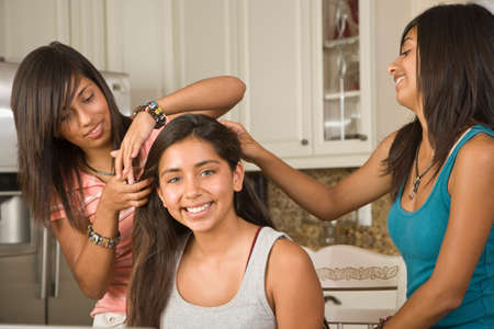teenaged girls: Hispanic teenaged girls fixing friend's hair
