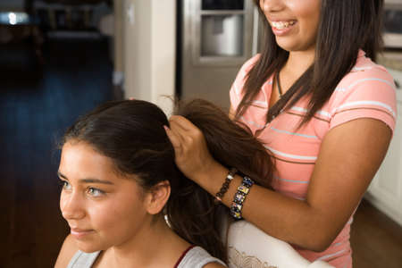 attired: Hispanic girl fixing friend's hair LANG_EVOIMAGES