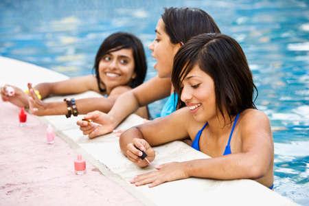 teenaged girls: Hispanic teenaged girls painting fingernails in swimming pool
