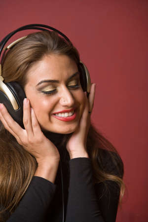 enclosing: Middle Eastern woman listening to headphones