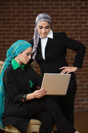 blabbing: Middle Eastern businesswomen looking at laptop