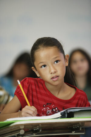 longshot: Asian girl at desk in classroom