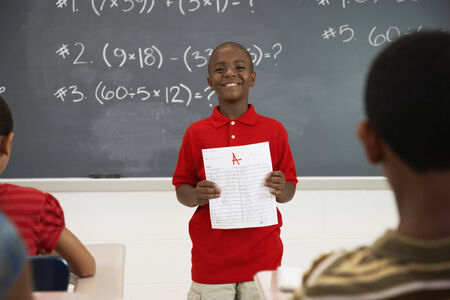 tutoring: African American boy holding paper in front of class