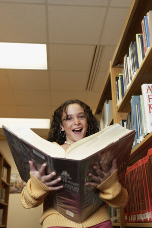 schoolroom: Girl holding library dictionary