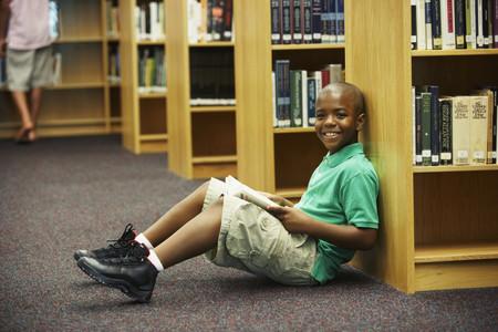 mujer hijos: Muchacho afroamericano que sostiene libro de la biblioteca