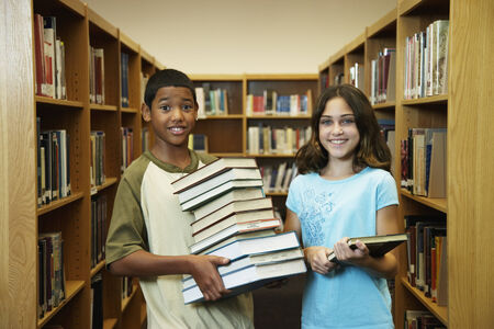 Multi-ethnic students holding library books Banco de Imagens